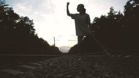 Um cara dança krump, faz um movimento legal à mão perto da trilha ferroviária no pôr do sol, em câmera lenta vídeos de arquivo