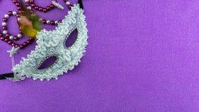 Um carnaval ou uma máscara branca festiva, bonita do carnaval no fundo de papel colorido bonito imagem de stock
