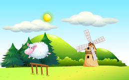 Um carneiro que salta na cerca com um moinho de vento na parte traseira Imagens de Stock Royalty Free