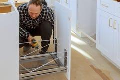 Um carpinteiro está construindo um escaninho de lixo das gavetas na cozinha imagens de stock