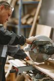 Um carpinteiro, no uniforme, trabalha com um torno que corta uma barra da madeira imagens de stock royalty free