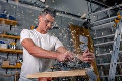 Um carpinteiro trabalha no woodworking a máquina-instrumento Vê detalhes da mobília com uma serra circular Processo de ver as peç fotografia de stock royalty free