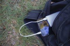 Um carregador portátil carrega a tabuleta Põe o banco com cabo no saco, na perspectiva da natureza Fotografia de Stock Royalty Free