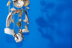 Um carrilhão de vento com shell em um fundo azul em uma vara em uma terra azul Fotografia de Stock Royalty Free