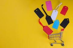 Um carrinho de compras com etiquetas e os preços multi-coloridos em um fundo amarelo brilhante de um conceito preto de sexta-feir fotos de stock