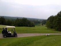 Um carrinho de golfe estacionado em um trajeto do campo de golfe imagem de stock