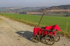 Um carrinho de mão com uma cobertura vermelha imagens de stock