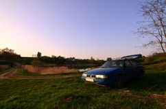 Um carro azul em um fundo de uma paisagem rústica com um campo selvagem do bastão e um lago pequeno A família veio descansar na n fotografia de stock royalty free