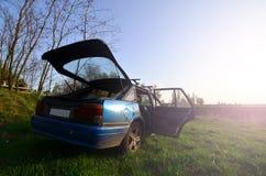 Um carro azul em um fundo de uma paisagem rústica com um campo selvagem do bastão e um lago pequeno A família veio descansar na n fotografia de stock