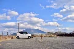 Um carro bonito estacionou no porto de Kagoshima, perto do vulcão de Sakurajima imagem de stock royalty free