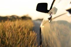 Um carro branco estacionado na borda da estrada com fundo do campo do borrão fotos de stock