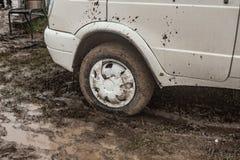 Um carro colou na lama no outono Fotos de Stock