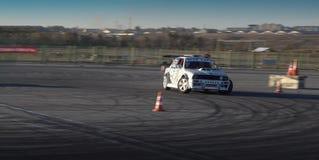 Um carro de competência da tração na ação com os pneus de fumo na mostra fotos de stock royalty free