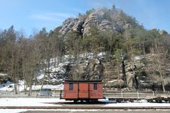 Um carro de estrada de ferro velho pequeno na frente de um contexto da rocha fotografia de stock royalty free