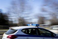 Um carro de polícia de pressa e um fundo obscuro Imagens de Stock Royalty Free
