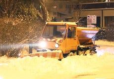 Um carro do serviço técnico com uma grande escavadora limpa as estradas de cidade da neve e polvilha-as com a areia Destravando a fotos de stock royalty free