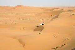 Um carro no meio das dunas de areia Fotografia de Stock