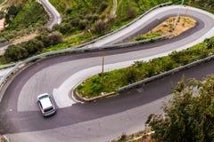 Um carro que toma um afiado gerencie sobre uma estrada da serpentina do enrolamento perto de Savo Imagem de Stock