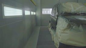 Um carro recentemente pintado está em uma cabine de pulverizador Pintura profissional do carro, SUV, movimento lento video estoque
