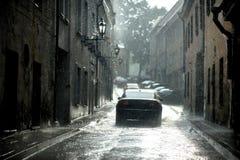 Um carro sob uma chuva na cidade imagem de stock royalty free