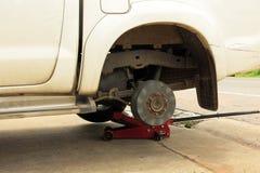 Um carro sujo branco sem um pneumático em reparar o processo fotografia de stock royalty free
