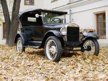 Um carro velho na jarda que é coberto com as folhas de bordo amarelas imagens de stock royalty free