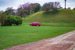 Um carro vermelho na tampa verde da grama em inclinações do castelo de Dôvar imagens de stock