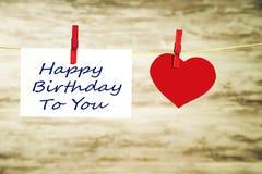 Um cartão branco e um coração vermelho que penduram em uma corda, prendida com as curvaturas vermelhas com o feliz aniversario da imagem de stock royalty free