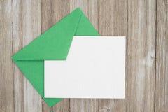 Um cartão branco vazio gravado com o envelope verde no wo resistido imagens de stock
