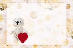 Um cartão com um urso minúsculo fazer crochê que guarda um coração feito a mão fazer crochê para o dia de Valentim Fundo romântic Fotografia de Stock