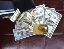 Um cartão de banco do crédito descansa em um grupo de dólares no fundo de uma cadeira de couro e de uma carteira Fotos de Stock Royalty Free