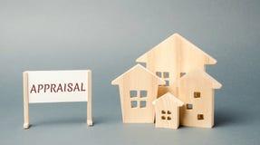 Um cartaz com a avaliação da palavra e uma casa de madeira diminuta Casas dos bens imobili?rios?, planos para a venda ou para o a imagem de stock
