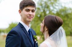 Um casal bonito nos vestidos de casamento, levantando para um tiro da foto em uma vila bielorrussa Fundo verde Fotos de Stock