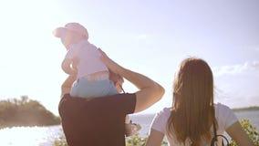 Um casal com um suporte do bebê e olhar no rio filme