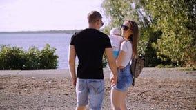 Um casal com um suporte do bebê e olhar para o rio video estoque