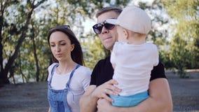 Um casal com uma criança está andando ao longo da terraplenagem filme