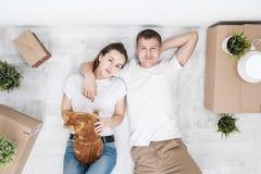 Um casal novo com um gato vermelho, um homem e uma mulher, está sentando-se no assoalho em uma sala brilhante contra imagens de stock royalty free