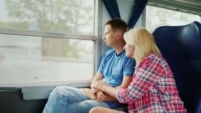Um casal novo está viajando em um trem Junto olham para fora a janela vídeos de arquivo