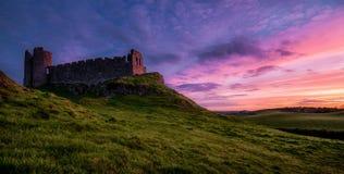 Um castelo velho bonito que olha fixamente em uma apreciação e em um por do sol róseo Fotos de Stock