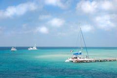 Um catamarã e o outro barco perto da costa em Isla Mujeres, México imagens de stock