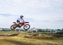 Um cavaleiro da motocicleta participa em uma raça do motocross Saltos no trampolim Foto de Stock Royalty Free