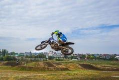 Um cavaleiro da motocicleta participa em uma raça do motocross Saltos no trampolim Fotografia de Stock