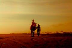 Um cavaleiro e um guia do cavalo Imagens de Stock Royalty Free