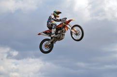 Um cavaleiro pelo MX da motocicleta voa Fotografia de Stock