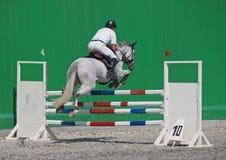Um cavaleiro salta sobre o obstáculo Fotos de Stock Royalty Free