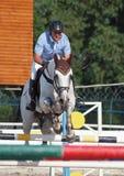 Um cavaleiro salta sobre o obstáculo Imagem de Stock