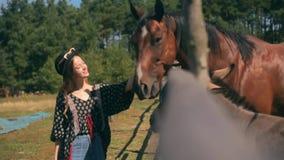 Um cavalo come de uma menina a moça da mão que do ` s alimenta seu cavalo fora de sua mão Menina adolescente bonita do viajante q filme