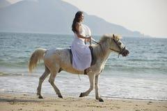 Um cavalo de equitação da mulher na praia Fotografia de Stock Royalty Free