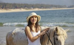 Um cavalo de passeio da mulher na praia Fotografia de Stock