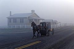 Um cavalo e um transporte passam uma casa da escola de Amish imagens de stock royalty free